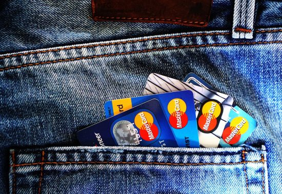 An image of multiple credit cards sticking out of a back pocket