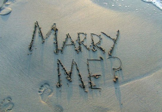 An image of writing in the sand on a beach saying 'Marry Me?'